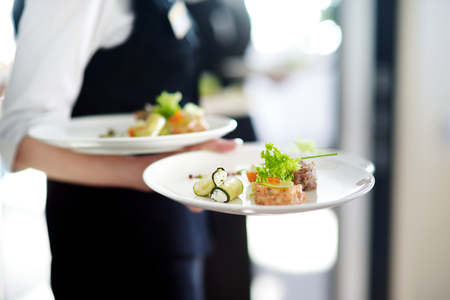 Waiter carrying plates with meat dish on some festive event, party or wedding reception Stock fotó