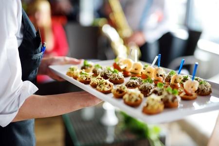 Cameriere che porta piatti con piatto di carne su qualche evento festivo, festa o ricevimento di nozze Archivio Fotografico - 47847698