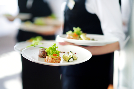 Waiter carrying plates with meat dish on some festive event, party or wedding reception 스톡 콘텐츠