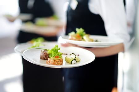 Waiter portant sur certaines réception festive événement, de partie ou le mariage avec plaques plat de viande
