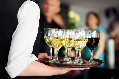 skoal: Waitress holding a dish of champagne and wine glasses at some festive event, party or wedding reception