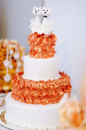 wedding table decor: White wedding cake decorated with orange sugar flowers and two sugar kitties on top Stock Photo