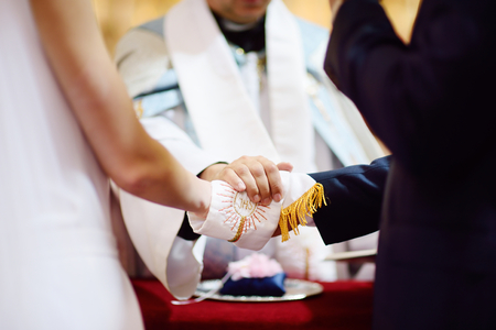 sotana: Boda cat�lica: la novia y las manos del novio envuelto en la sotana del sacerdote Foto de archivo