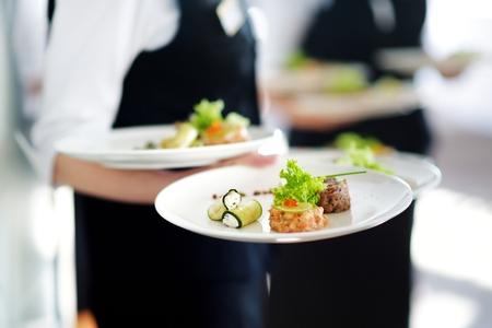 Cameriere che porta piatti con piatto di carne su qualche evento festivo, festa o ricevimento di nozze Archivio Fotografico - 47854202