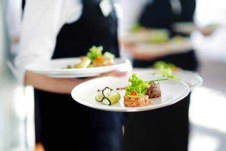 banquet table: Waiter carrying plates with meat dish on some festive event, party or wedding reception Stock Photo