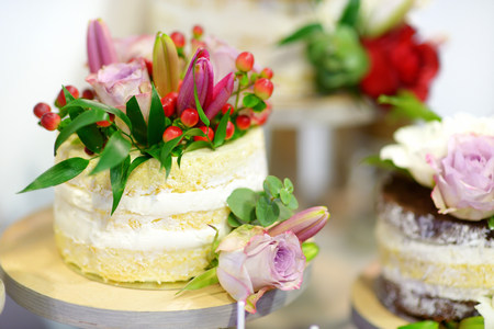 wedding table decor: White wedding cake decorated with natural flowers