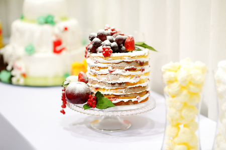 wedding table decor: Delicious wedding cake decorated with fruits