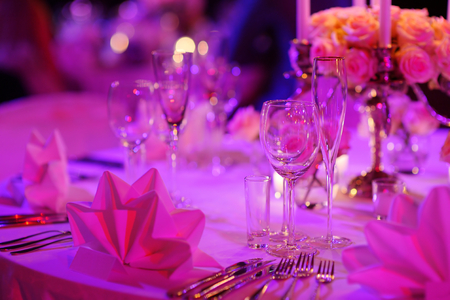 events: Table set for an event party or wedding reception in purple light Stock Photo