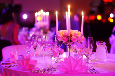reception desk: Table set for an event party or wedding reception in purple light Stock Photo
