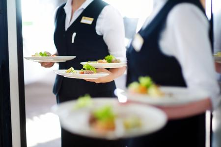 웨이터는 어떤 축제 이벤트, 파티 또는 결혼식 리셉션에 고기 요리와 접시를 들고 스톡 콘텐츠