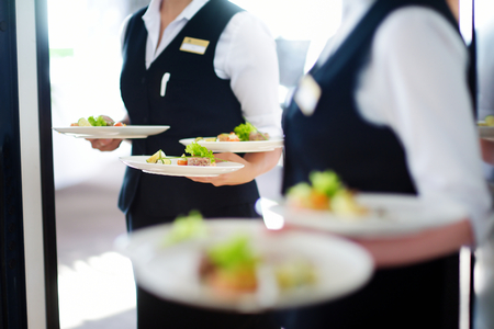 waitresses: Waiter carrying plates with meat dish on some festive event, party or wedding reception Stock Photo