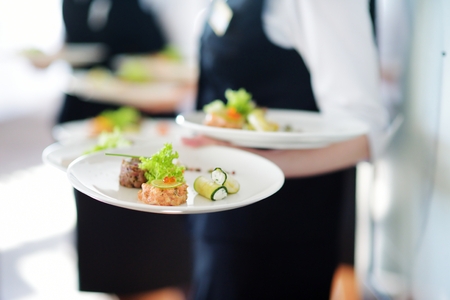 restaurant dining: Waiter carrying plates with meat dish on some festive event, party or wedding reception Stock Photo