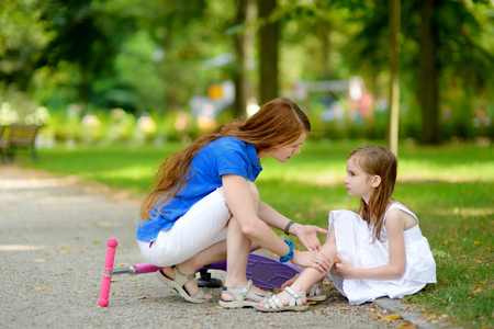 Mother comforting her daughter after she fell while riding her scooter at summer park Banque d'images