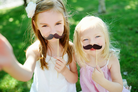 white moustache: Adorable little girls playing with paper moustaches on a stick and other party accessories