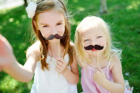 bigote: Ni�as adorables que juegan con los bigotes de papel en un palo y otros accesorios de fiesta
