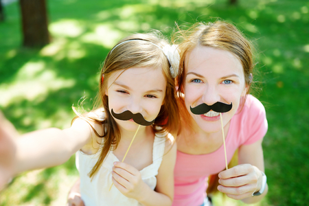 mom daughter: Mother and daughter playing with paper moustaches on a stick and other party accessories Stock Photo