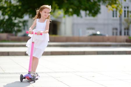 Adorabile bambina che indossa abito bello cavalcare il suo scooter in un parco di estate Archivio Fotografico