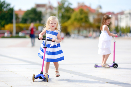 scooter: Two adorable little sisters wearing beautiful dresses riding their scooters in a summer park Stock Photo