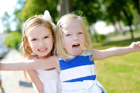 Two little sisters making funny faces outdoors
