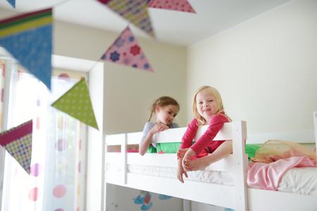 Twee kleine zusters dollen, spelen en plezier in twin stapelbed op zonnige zondagochtend
