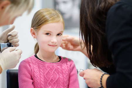 ears: Adorable little girl having ear piercing process with special equipment in beauty center by medical worker
