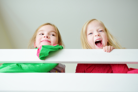 bunk bed: Two little sisters fooling around, playing and having fun in twin bunk bed on sunny sunday morning