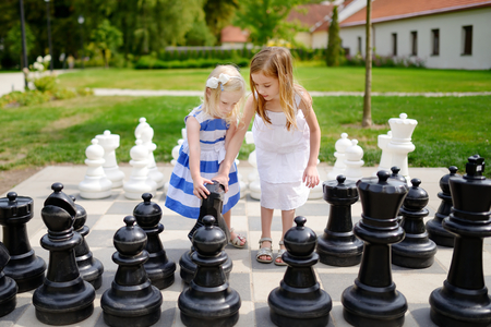Two little sisters playing giant chess outdoors Foto de archivo