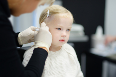 Adorable little girl having ear piercing process with special equipment in beauty center by medical worker