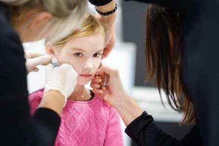 ビューティー センターでは医療従事者での特別な装置とプロセスをピアス耳を持つ愛らしい少女 写真素材