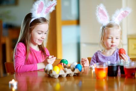 huevos de pascua: Dos peque�as hermanas que pintan los huevos de Pascua coloridos en el hogar Foto de archivo