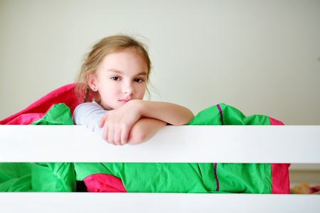bunk: Adorable little girl having fun in twin bunk bed on sunny sunday morning