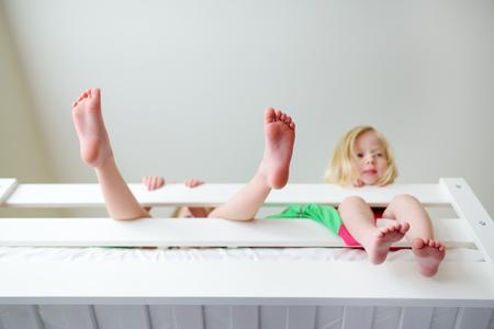 Zwei kleine Schwestern herumalbern, spielen und Spaß in zwei Etagenbett an sonnigen Sonntagmorgen