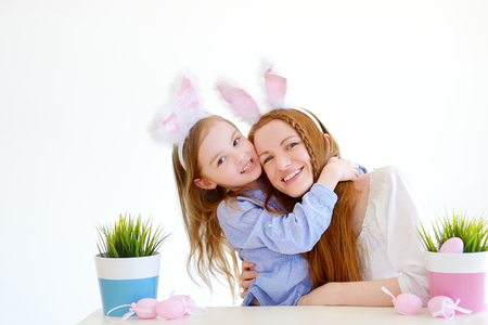 mum and daughter: Adorable little girl and her mother wearing bunny ears on Easter day