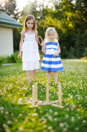 to toss: Two cute little sisters playing ring toss game outdoors on beautiful summer day Stock Photo