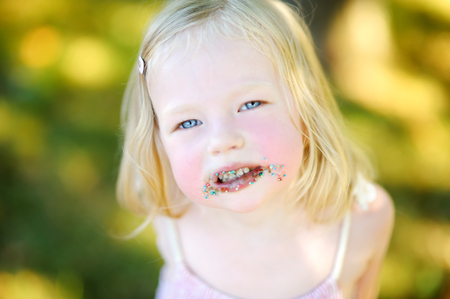 smeary: Sweet little girl with messy face eating waffle Stock Photo