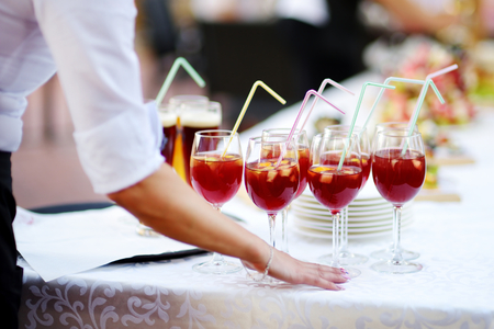 skoal: Waitress holding a dish of sangria and wine glasses at some festive event, party or wedding reception