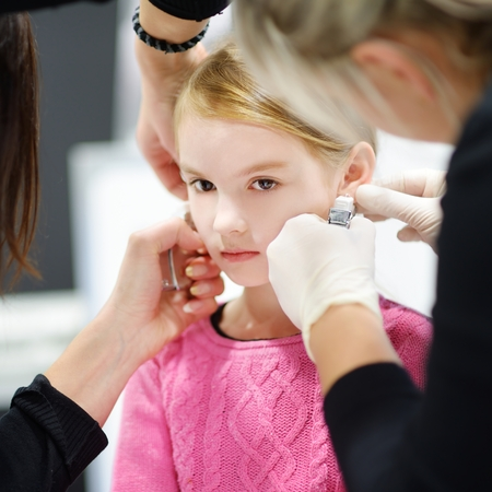 pierced ears: Adorable little girl having ear piercing process with special equipment in beauty center by medical worker