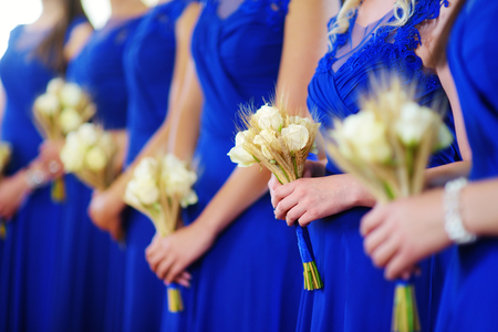 Row of bridesmaids wearing blue dresses holding wedding bouquets at wedding ceremony