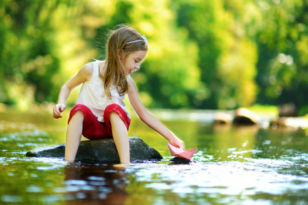 girl in dress: Cute little girl playing with paper boat by a river on warm and sunny summer day