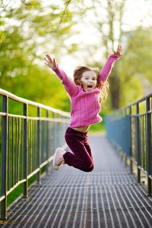 persona saltando: Niña divertida que salta con alegría y felicidad al aire libre en hermoso día de verano Foto de archivo