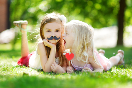 moustache: Adorable little girls playing with paper moustaches on a stick and other party accessories