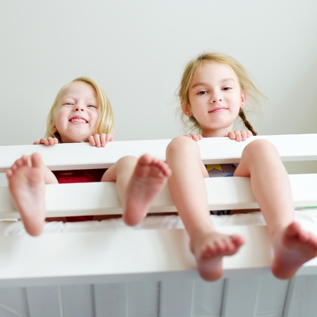 bunk: Two little sisters fooling around, playing and having fun in twin bunk bed on sunny sunday morning