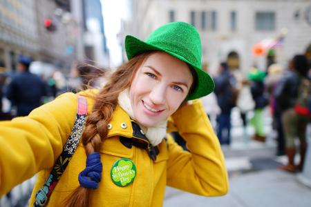 뉴욕시 5 번가에 연간 성 패트릭의 날 퍼레이드 동안 그녀의 스마트 폰과 함께 셀카를 복용하는 젊은 관광 스톡 콘텐츠