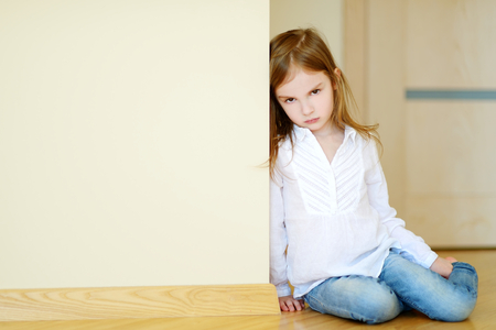girl alone: Sad little girl sitting on a floor at home