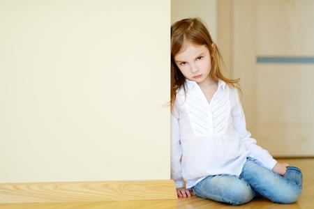 petite fille triste: Sad petite fille assise sur un plancher à la maison Banque d'images