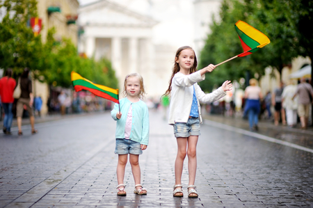 lithuanian: Two adorable little sisters holding Lithuanian flags in Vilnius, the capital of Lithuania Stock Photo