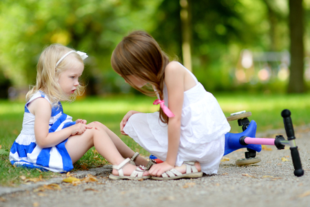 sad child: Little girl comforting her sister after she fell while riding her scooter at summer park
