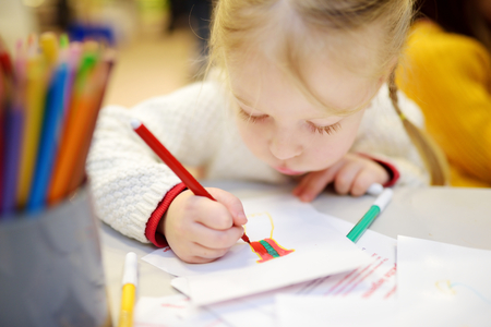 once person: Cute preschooler girl drawing a picture with colorful pencils Stock Photo