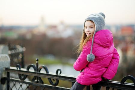 Nettes kleines Mädchen, das einen Zaun auf schönen Tag im Herbst Klettern im Freien Standard-Bild
