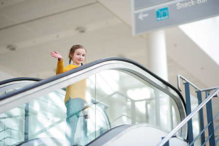 view of a staircase in a shop: Cute little child standing on moving staircase in airport Stock Photo